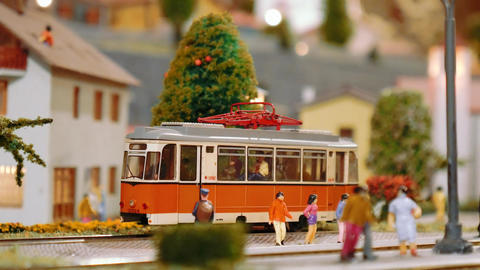 Model tram arrives then two trains pass by on a diorama Footage
