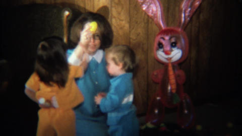 1974: Vintage mom plays with kids at Easter with doll in background Footage