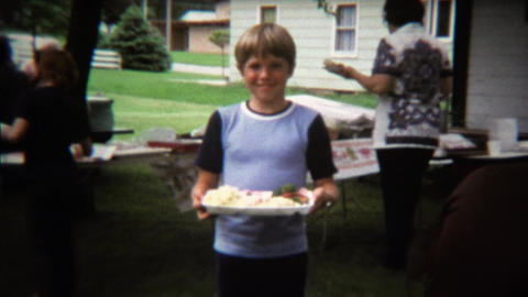 1973: Boy licking his lips anticipating eating plate of outdoor picnic food Footage