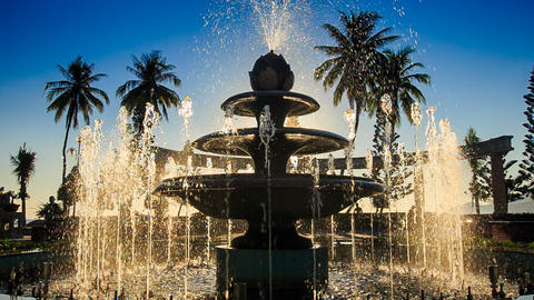 camera moves around cascade fountain changing jets in park Footage