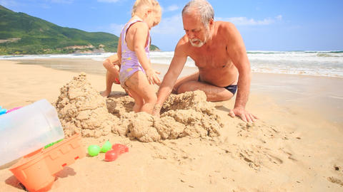 Grandpa Kids Build Sand Castle on Beach by Wave Surf Footage