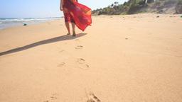Slim Woman in Long Red Dress Leaves Footprints on Wet Sand Footage