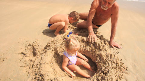 Little Girl Plays in Sand Hole by Grandpa Boy on Beach Footage