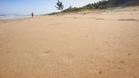 Camera Moves along Footprints Left on Wet Sand Footage