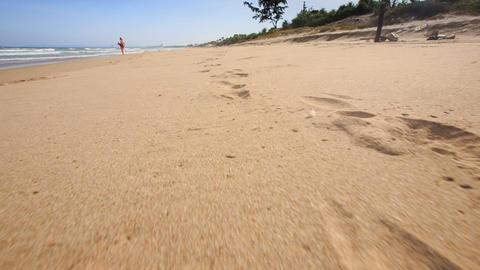 Camera Moves along Footprints Left on Wet Sand Footage