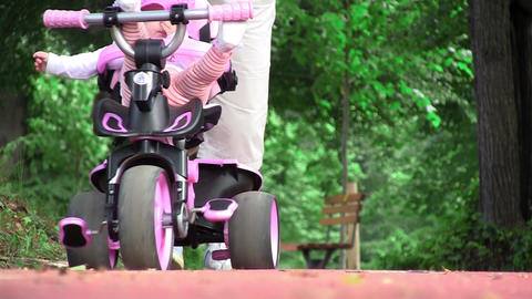 Grandmother walking her niece with a tricycle in park 01 Footage