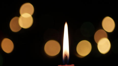 Candle with black background that is seen Christmas lights 3 Footage