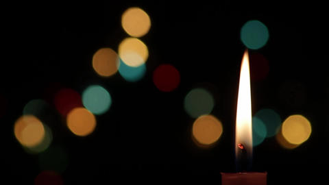 Candle with black background that is seen Christmas lights 5 Footage