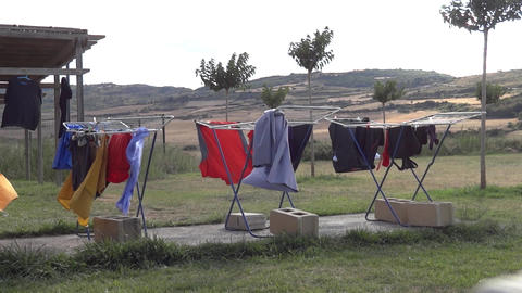 Clothes hanged out to dry on a clothes dryer, a cottage somewhere. Outside the w Footage