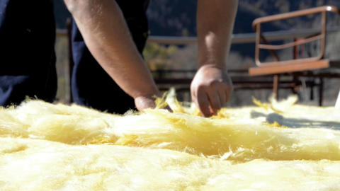 Piece of mineral wool is cut with a cutter in appropriately sized pieces 4f Live Action