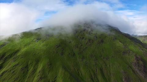 Clouds flying over mountain top, aerial view Footage