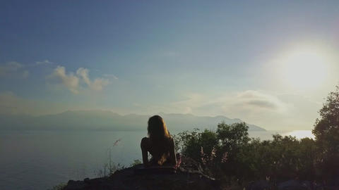Drone Approaches Girl Resting on Cliff under Morning Sunlight Footage