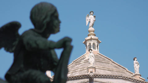 Angel statues on the baptistery of Bergamo, bronze angel in foreground Live Action