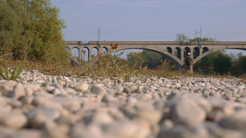 Fisherman walks to the river while a train crosses a bridge Footage