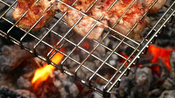 Cooking meat over an open fire. Smoke and flames from smoldering charcoal. Loop Footage