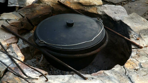 Uzbek national dish pilaf in a large cast-iron cauldron on the fire Footage
