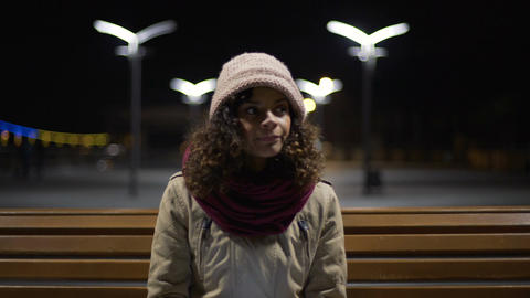 Beautiful girl sitting alone at night bus station, browsing schedule on gadget Live Action