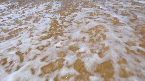Foamy waves rolling fast onto coast with golden sand and washing back to ocean Footage