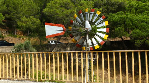 Wind turning slowly blades of weathervane windmill by road, weather forecast Live Action