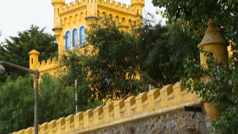 Small castle tower painted in yellow behind stone roofed wall, vertical panorama Footage