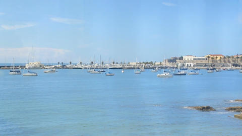 Beautiful blue water harbor with moored sailing boats, view from moving train Footage