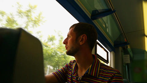 Guy looking through window on train, young man traveling by railway transport Footage