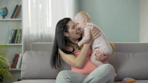 Excited young mother actively playing with her little daughter at home, family Footage