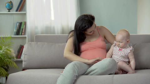 Pregnant woman touching belly tenderly, playing with sweet little baby girl Footage