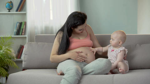 Playful sweet baby girl clapping pregnant mother on big belly, happy maternity Footage