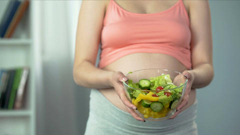 Pregnant woman holding bowl of vegetable salad rich in vitamins and nutrients Footage