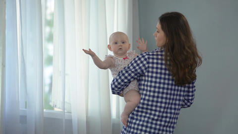 Baby girl looking into camera and waving hands, loving mother comforting child Footage