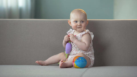 Baby smiling and playing with toys on sofa, infant enjoying comfort in diapers Footage