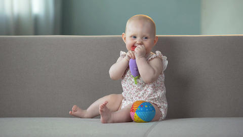 Cute baby tasting colorful toy, discovering world in good mood, infant tooth gel Footage