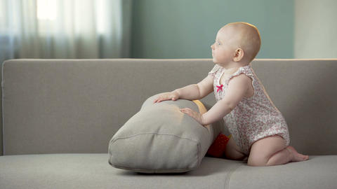 Funny happy baby girl jumping on sofa, discovering world in comfortable diapers Footage