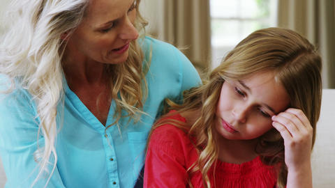 Mother consoling her daughter in living room Live Action