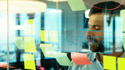 Male executive looking at sticky notes on glass Live Action