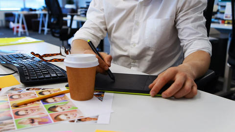 Male graphic designer working on graphic tablet at desk Live-Action