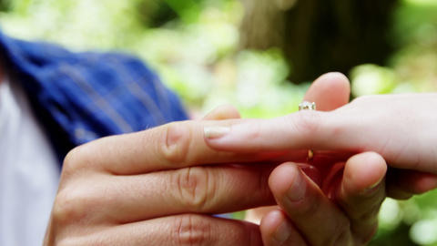 Close-up of putting engagement ring on woman hand Live Action
