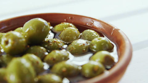 Green olives and herbs in vinegar Stock Video Footage