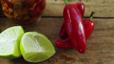 Ingredients red chili pepper, red olives and lemon kept on wooden table Footage