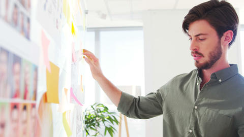 Executive reading sticky notes on glass wall Live Action