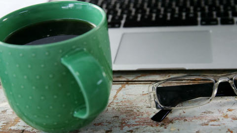 Coffee mug, laptop, spectacle on wooden plank Live Action