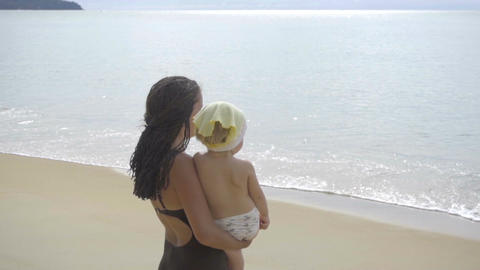 Mom with a two-year-old daughter walking along the sandy beach Footage