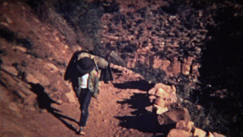 1972: Boy walking up dusty rocky mountain trail with backpack Footage