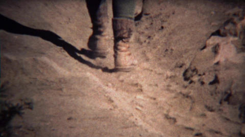 1972: Worn boots closeup walking up dusty dry desert hiking trail Footage