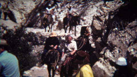 1972: Horse riding group coming down steep single dry track trail Footage