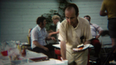 1973: Mature man getting extra cake at summer family reunion picnic Footage