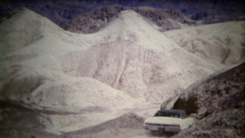 1972: Classic big car driving down steep hill in white desert dry wasteland Footage