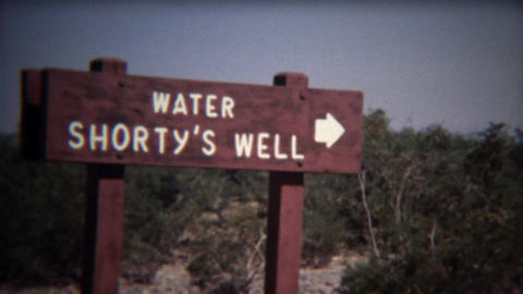 1972: Shorty's water well oasis in middle of dry scrub bush desert Footage