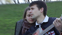 A guy sings a girl song and plays guitar on the date Stock Video Footage